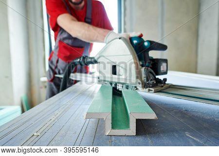 Drywall construction. worker sawing gypsum plasterboard by hand-held machine. Focus on gypsum