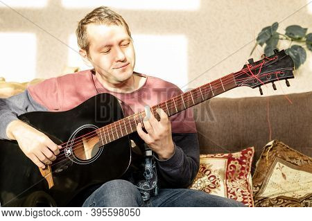 Portrait Of Smiling Man With Black Acoustic Guitar And Looking On Fretboard. Musician Learning New M