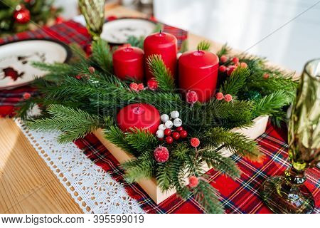 Red Color In The Design Of The New Years Table, On The Table Is A Christmas Tree Candles Plates Tabl