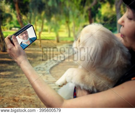 A Cheerful Veterinarian On A Mobile Phone Screen Advises A Little Dog While Walking In The Park With