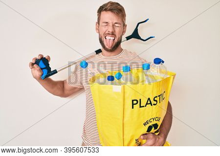 Young caucasian man holding recycling bag with plastic bottles and waste picker sticking tongue out happy with funny expression.