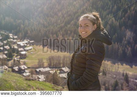 Smiling Woman Looking At Camera On Top Of Mountain Edge Cliff Enjoying Sun On Her Face.enjoying Natu