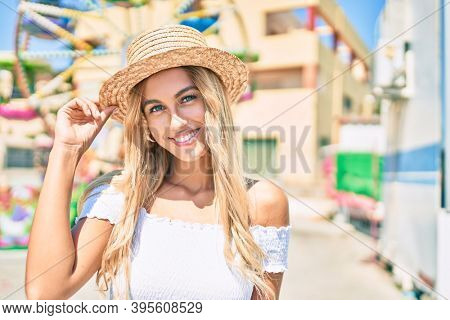 Young blonde tourist girl smiling happy looking to the camera at fairground.
