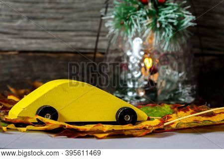 Yellow wooden toy car with cloorful leaves and holiday lantern