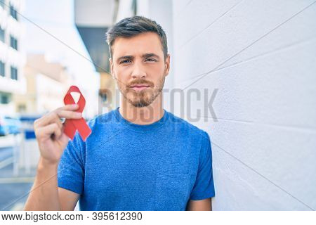 Young caucasian man with serious expression holding red hiv ribbon at the city.