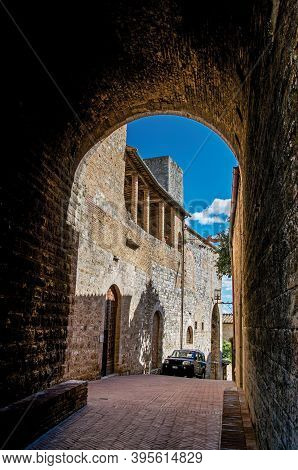 San Gimignano, Italy - May 13, 2013. View Of Dark Alleyway, Brick Building And Tower In San Gimignan
