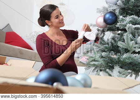 Merry Christmas, Happy Pregnant Woman Prepare The Christmas Tree, Hangs Up The Pink Shoes Waiting Fo