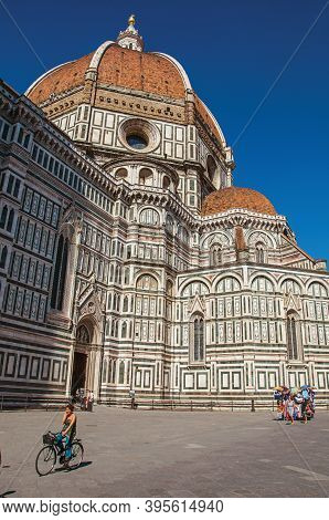 Florence, Italy - May 14, 2013. View Of Woman On Bicycle Next To The Cathedral Santa Maria Del Fiore