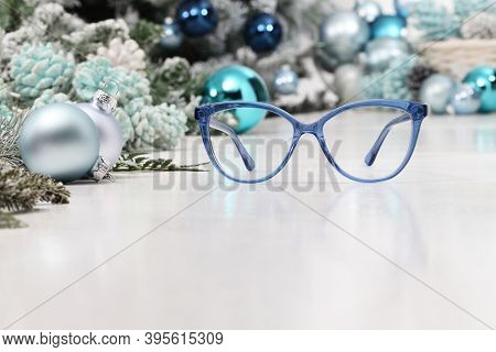 Christmas Eyeglasses Blue Spectacles Isolated On White Table With Balls And Decorations Useful As A