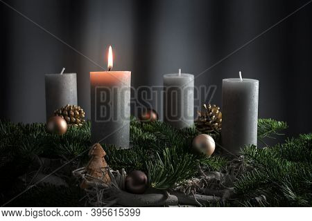 Four Candles, One Of Them Lit On An Advent Arrangement From Fir Branches And Christmas Ornaments, Ho