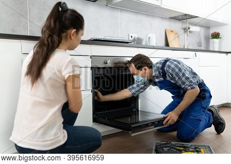 Kitchen Appliance Oven Repair By Handyman Technician In Face Mask
