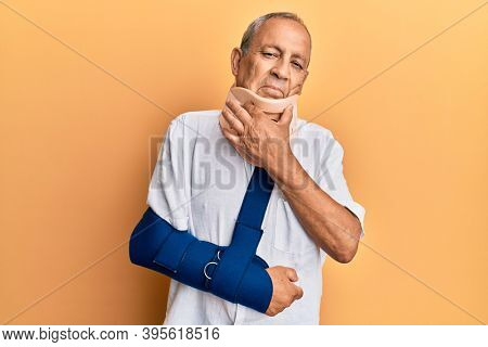 Handsome mature senior man wearing cervical collar and arm on sling looking confident at the camera smiling with crossed arms and hand raised on chin. thinking positive.