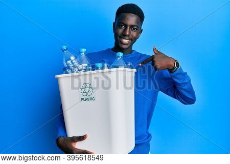 Young african american man holding recycling wastebasket with plastic bottles pointing finger to one self smiling happy and proud