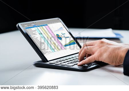 Analyst Using Spreadsheet Report On Tablet Computer