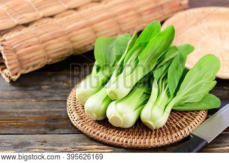 Fresh Bok Choy Or Pak Choi (chinese Cabbage) On Woven Rattan Plate With Wooden Background, Organic V