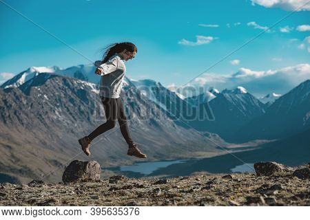 One Slim Sporty Girl Is Having Fun And Jumps Over The Stone In High Mountains. Active Tourism Concep