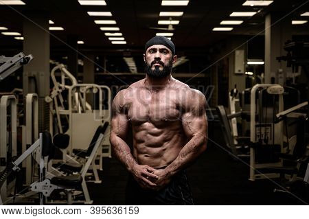 Strong Bearded Athlete In Bandana Posing In Dark Gym