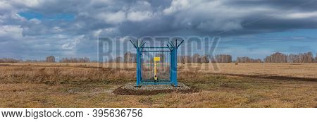 Panoramic Shot Of A Caged Industrial Gas Station With Barbwire On Top Of The Fence. Yellow Gas Pipe