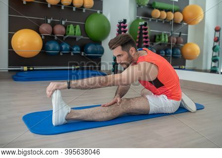 Bearded Young Male Bending Forward, Touching His Toes, Stretching Hamstring