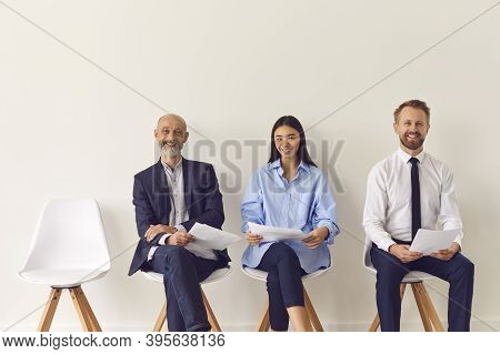 Three Positive Candidates Of Different Ages Sitting On Chairs Waiting For Job Interview