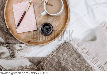 Cozy Flatlay With Wooden Tray, Cup Of Coffee Or Cocoa, Candle, Notebooks On White Sheets And Blanket