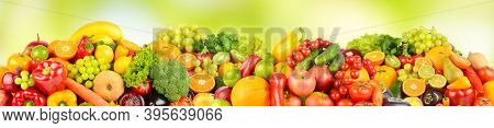 Wide pattern of ripe fruits and vegetables on green natural background.