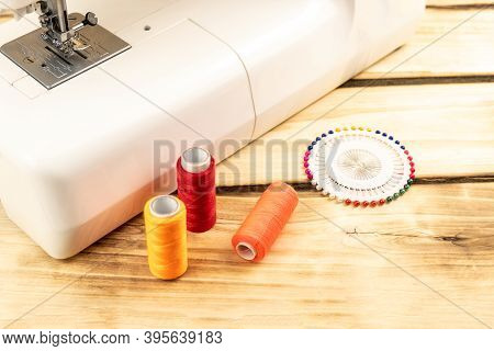 Spools Of Colored Thread, Sewing Pins Next To A Sewing Machine On A Wooden Background. Sewing And Ne