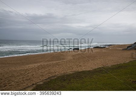 View Of Beach And Rocks From Green Grassy Area