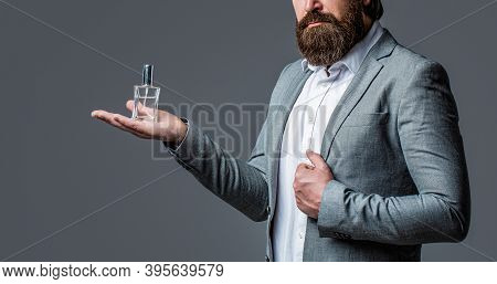 Man Perfume, Fragrance. Masculine Perfumery, Bearded Man In A Suit. Male Holding Up Bottle Of Perfum