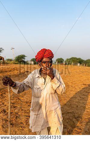 November 2019 Pushkar,rajasthan,india. Portrait Of A Rajasthani Man With Red Turban Smoking At Pushk