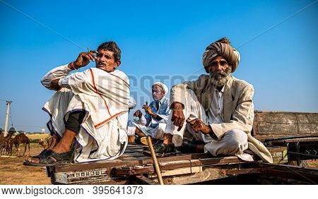 November 2019 Pushkar,rajasthan,india. A Group Of Three People Sitting On A Wooden Cart At Pushkar.