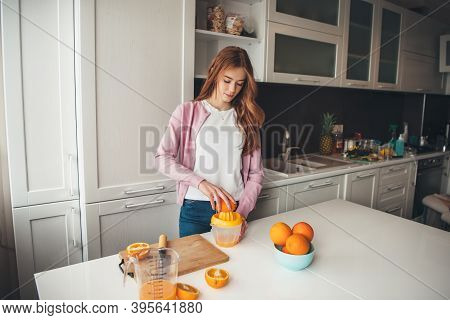 Caucasian Ginger Woman With Freckles Is Manually Squeezing Orange Juice In The Kitchen
