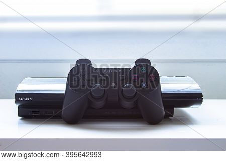 Calgary, Alberta, Canada. Nov. 19, 2020. A Playstation Ps3 With A Control Remote On A White Table.