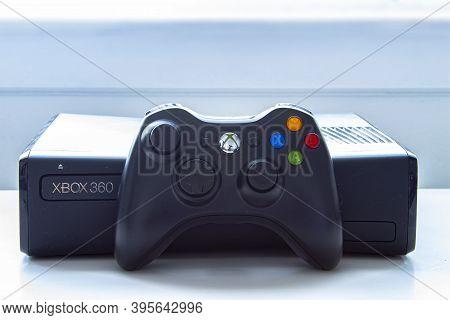 Calgary, Alberta, Canada. Nov. 19, 2020. An Xbox 360 Console With A Control Remote On A White Table.
