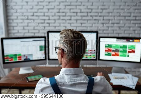 Rear View Of Middle-aged Trader Sitting By Desk In Front Of Pc And Analyzing Stock Market Chart, Whi
