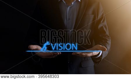 Businessman Holding A Concept In His Hands.the Silhouette Of Man Pushes The Word Vision.business Eco
