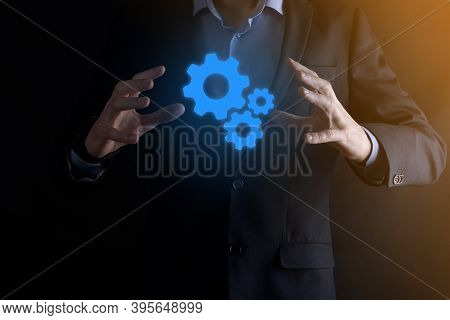 Business Man In Suit Holding Metal Gears And Cogwheels Mechanism Representing Interaction Teamwork C