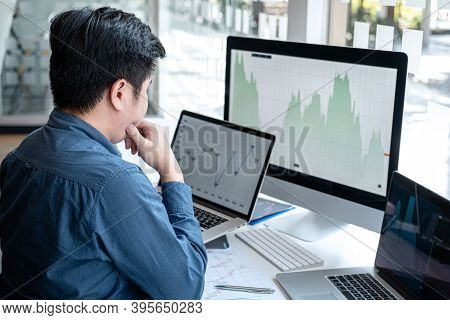 Stock Exchange Market Concept, Stock Broker Looking At Graph Working And Analyzing With Display Scre
