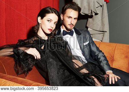 Beautiful elegant couple in fashionable evening clothes in a luxury apartment. Glamorous lifestyle. Fashion shot.
