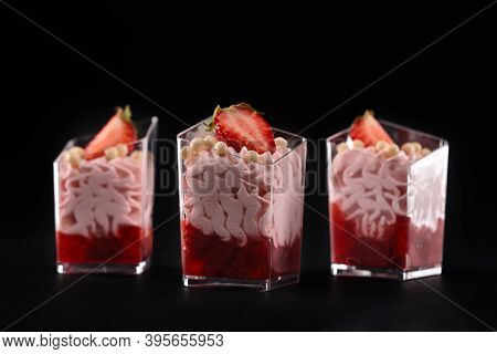 Whipped Pink Cream And Red Jam Decorated With Fresh Strawberries And White Crunchy Chocolate Balls O