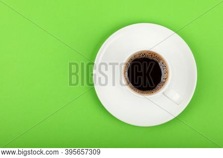 Close Up One White Cup Full Of Black Coffee On Saucer Over Green Background, Elevated Top View, Dire