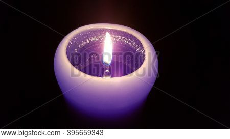 Candlelight Flame Closeup. Burning Fire Of Single Purple Candle In Darkness. Reflection Of Glowing F