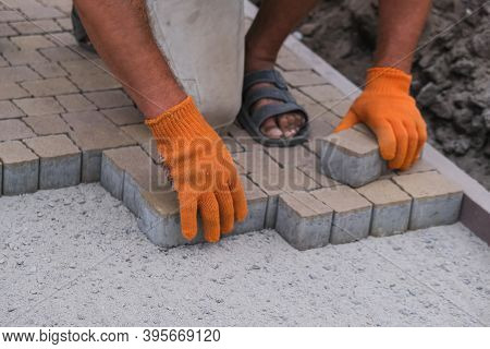 Construction Worker Installing And Laying Pavement Stones On Terrace, Road Or Sidewalk. Worker Using