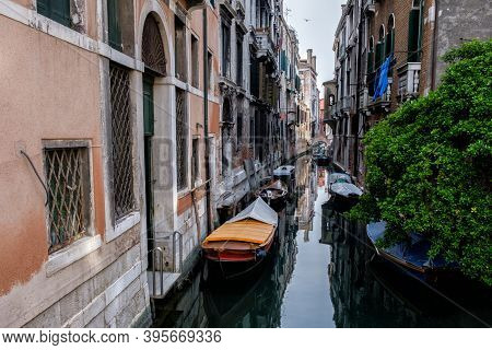 Narrow Canal Between Old Houses, Boats On Dark Water. Green Tree. Venice, Italy.