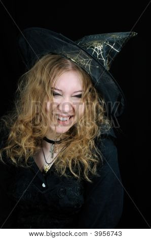 Cute young smiling halloween witch on black background poster