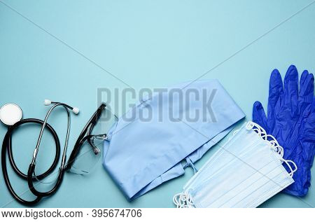 Textile Blue Cap, Disposable Medical Mask, Pair Of Gloves And Plastic Glasses On A Blue Background,