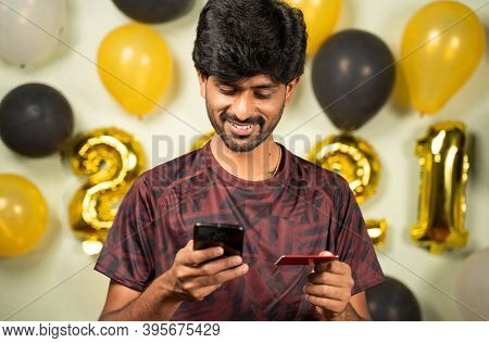 Young Man Busy In Purchasing Or Doing Online Payment On Mobile During Holiday Seasonal Sale On 2021