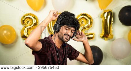 Young Man Enjoying By Listining Music On Headset Over 2021 New Year Decorated Background - Concept O
