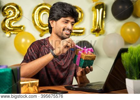 Young Man Opening Gift Box While On Video Call With 2021 New Year Decorated Background - Concept Of