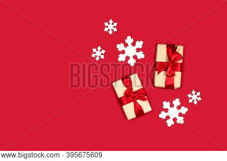 Gifts And White Snowflakes Flat Lay On Red Background Top View, Copy Space. Creative Christmas Compo